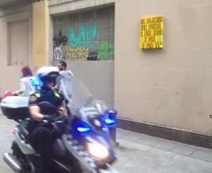 Un guardia urbano en moto pasa por delante del grafiti de la calle Ferlandina.