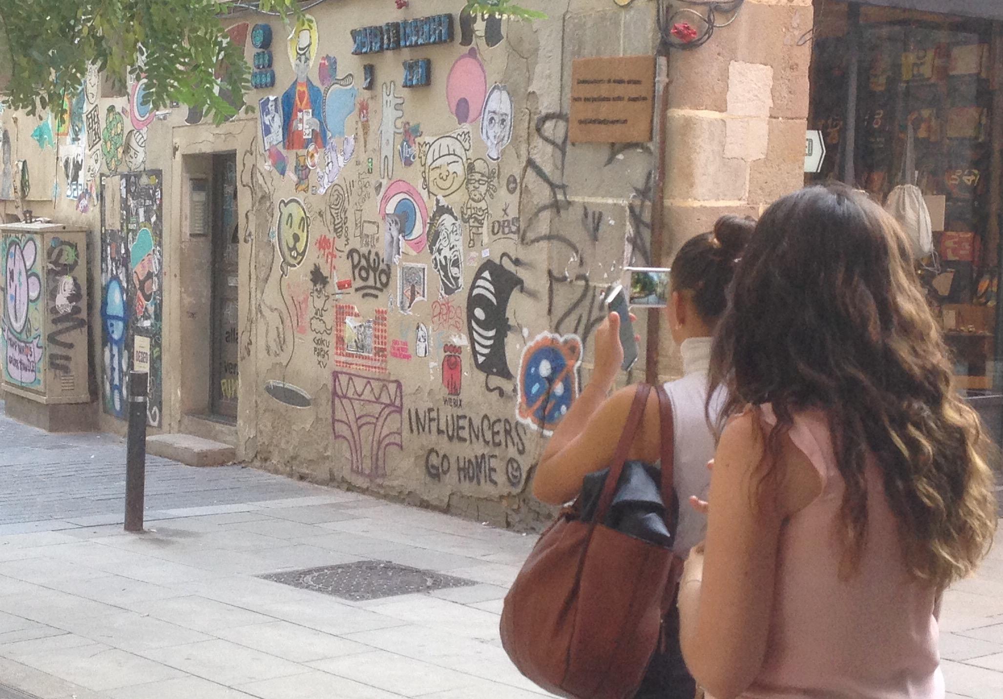 Una turista fotografia el mur d'Allada Vermell.