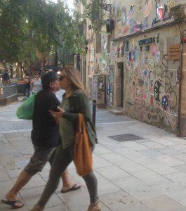 Dos vianants passant pel costat del mur.