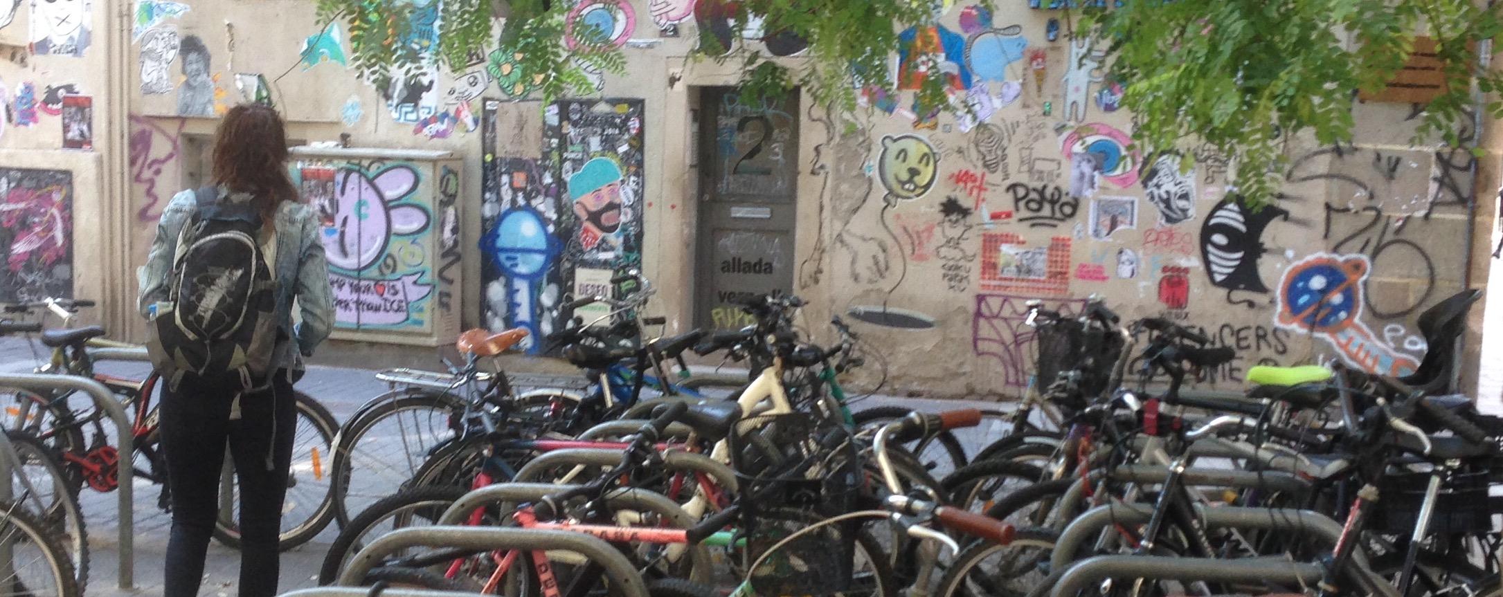 Una noia contempla el mur creatiu del carrer Allada Vermell, com si estigués en un museu a l'aire lliure.