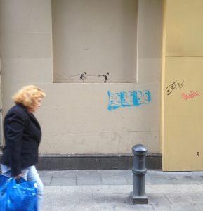 Una vecina camina ajena al duelo dibujado en la pared