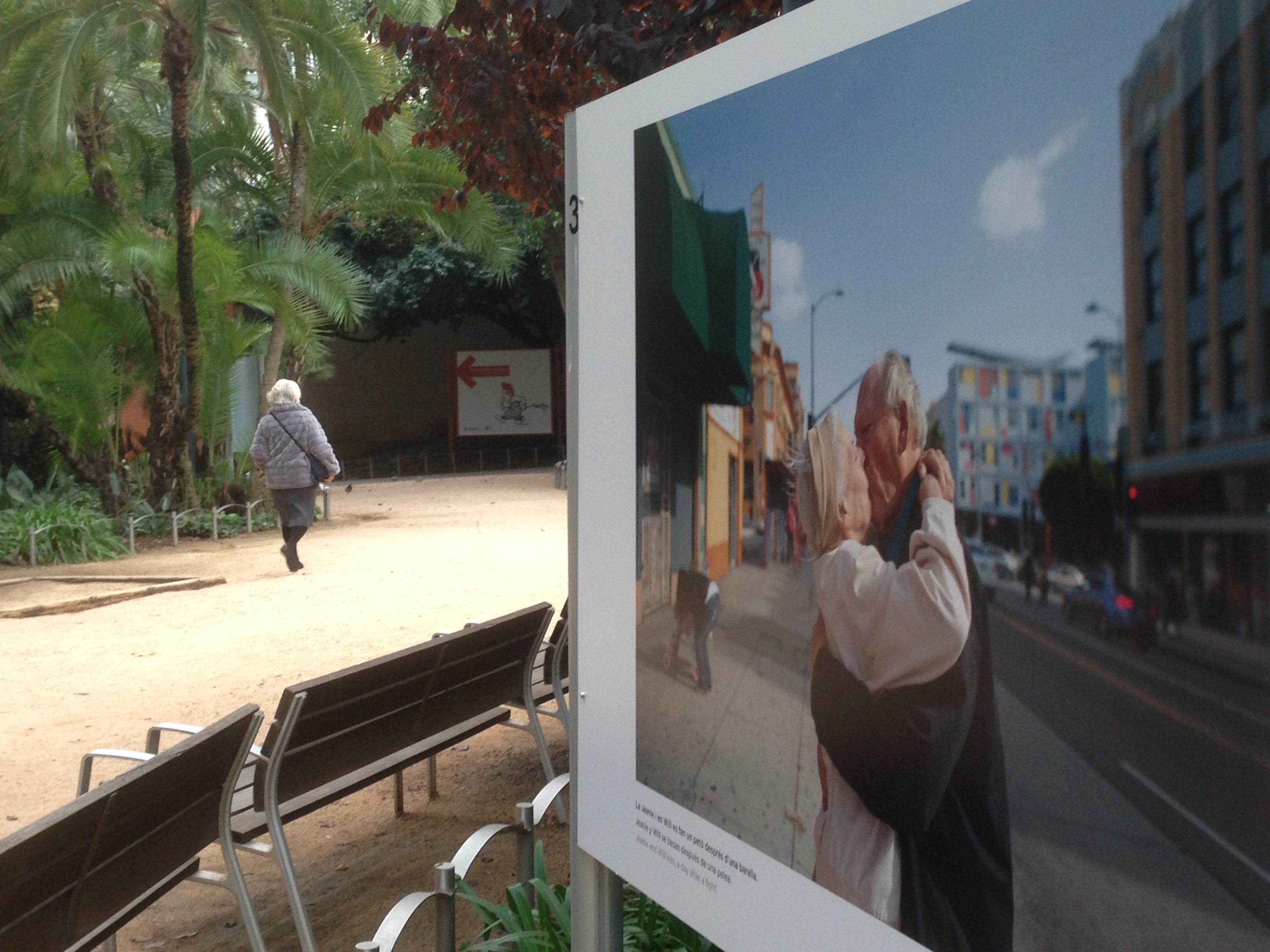 Una dona gran passant entre les fotografies de l'exposició.