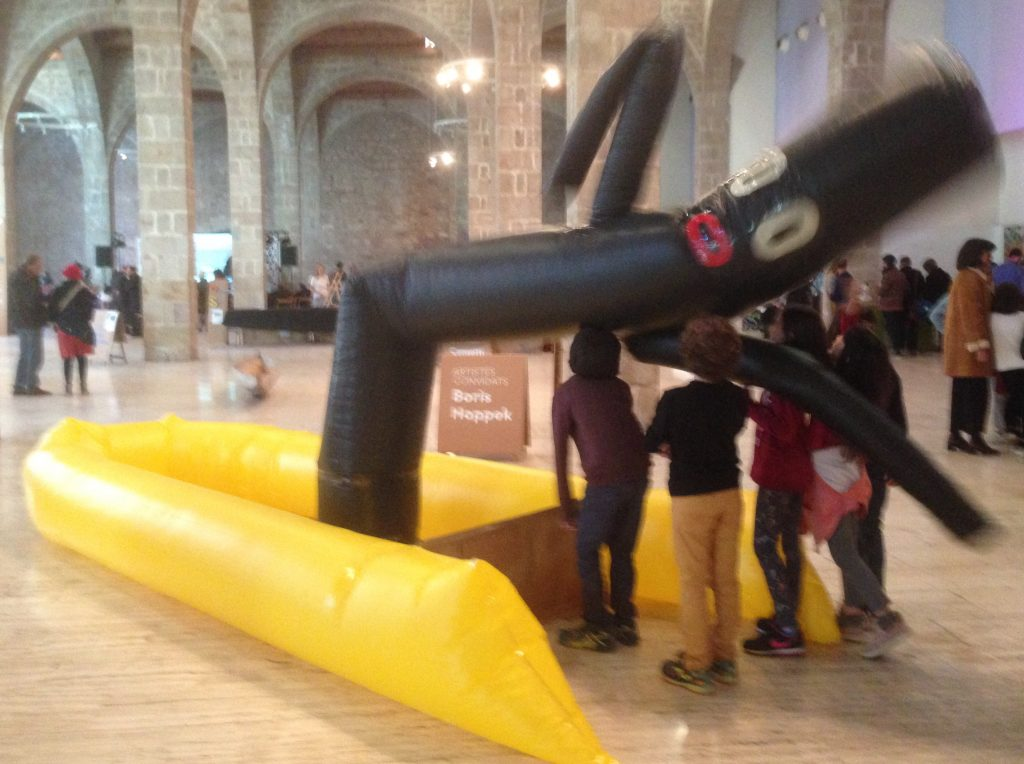 Nens jugant amb l'obra inflable que consciencia sobre els refugiats en pastera.
