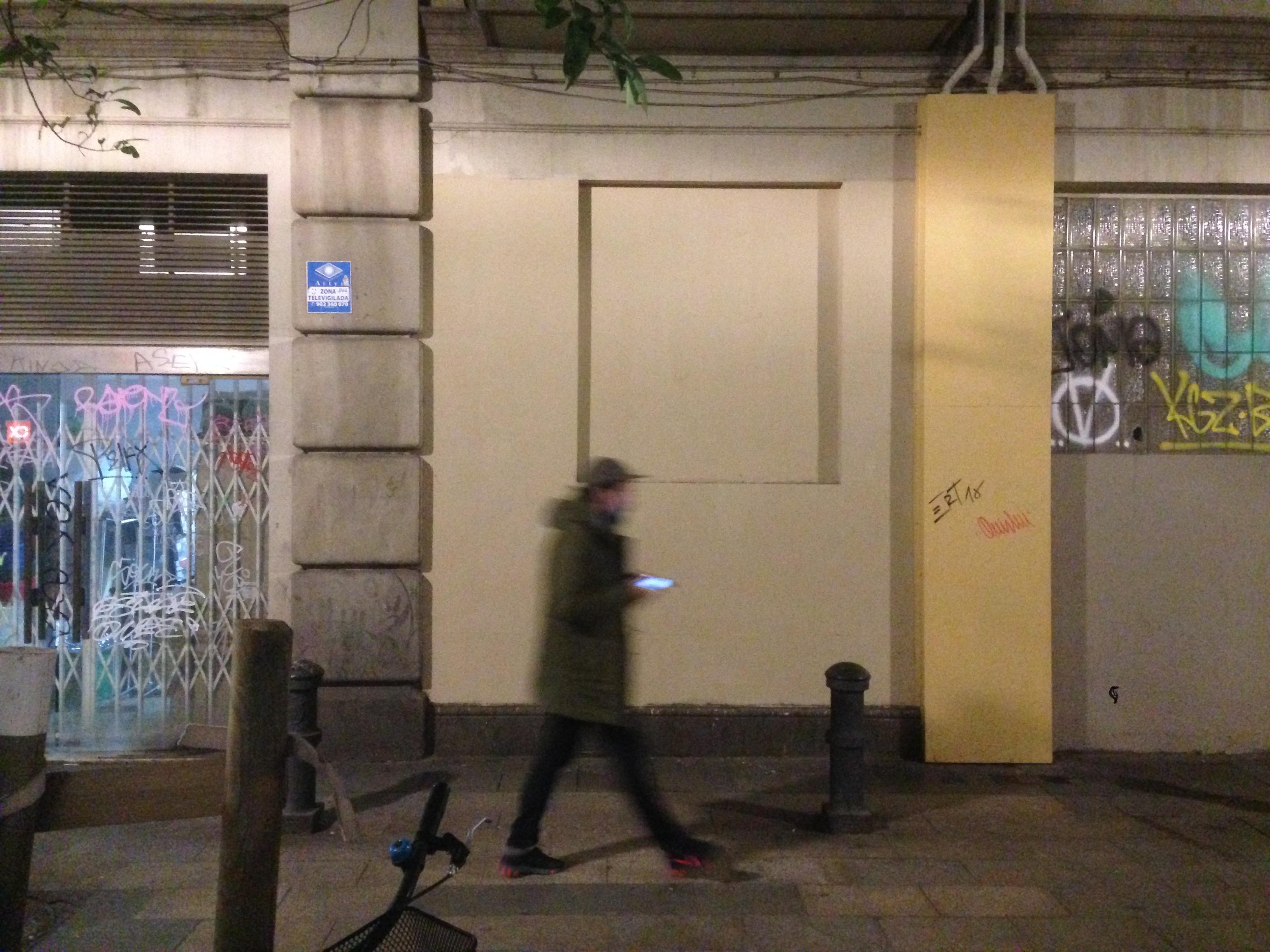 Un chico pasa, de noche, por la pared con el grafiti ya borrado.