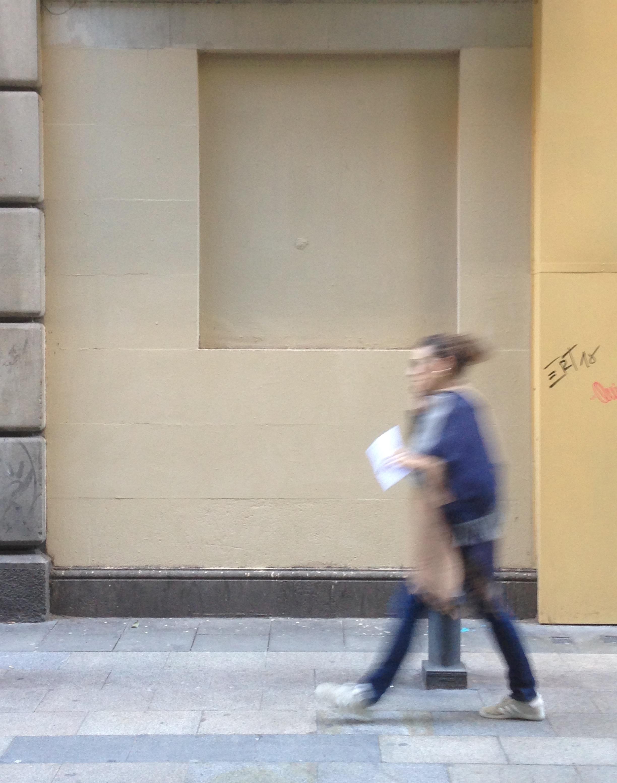 Un chica camina junto a la pared, donde ha desaparecido el rastro del duelo.